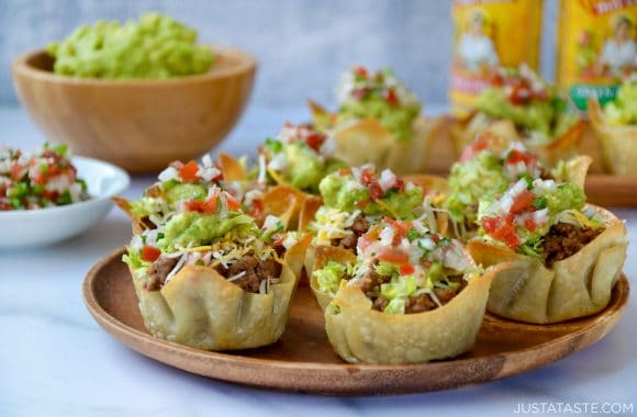 Homemade taco salad cups topped with guacamole and salsa on wood serving plate