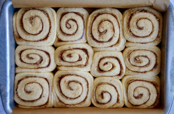 Top down view of unbaked cinnamon rolls in baking dish