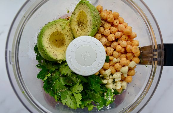 A clear food processor bowl containing avocado, chickpeas, garlic and herbs