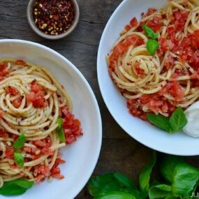White bowls containing pasta with no-cook tomato sauce, fresh basil and burrata garnished with red pepper flakes
