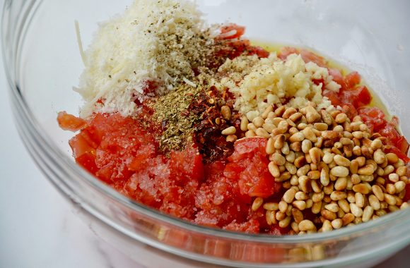Glass bowl containing no-cook tomato sauce ingredients: chopped tomatoes, cheese, spices, pine nuts and garlic