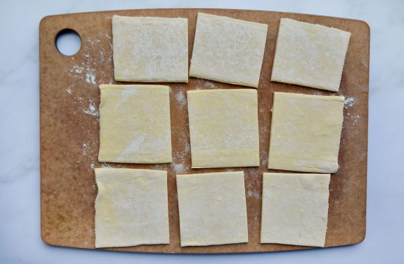 Cutting board containing nine puff pastry squares