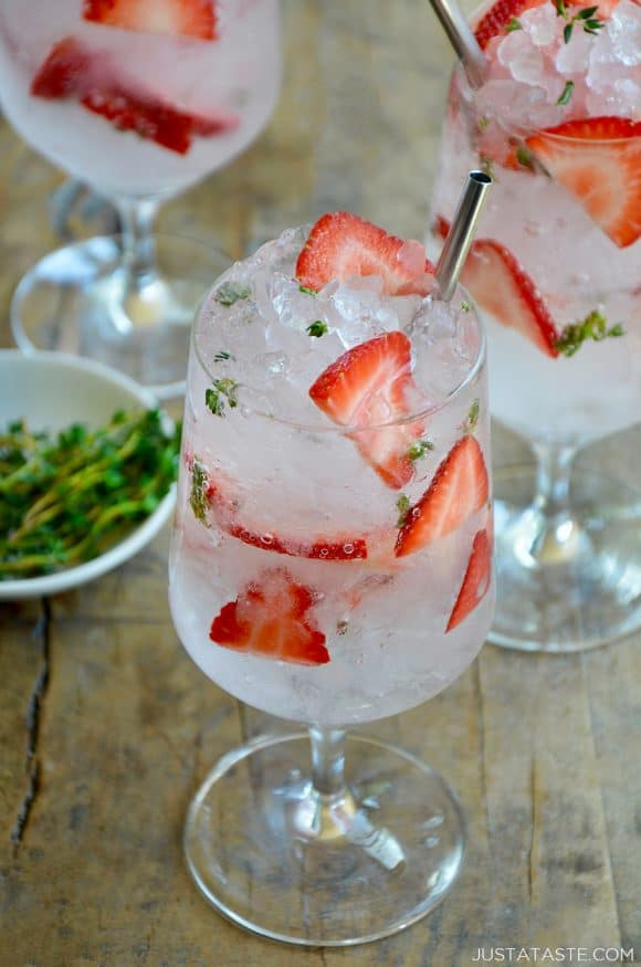 A Sparkling Strawberry Cocktail with fresh strawberries and thyme
