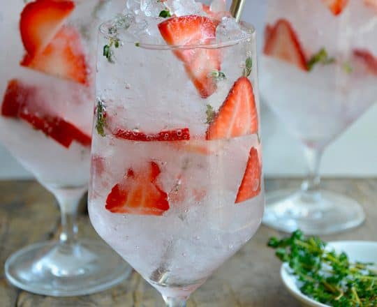 A clear glass containing sliced strawberries and crushed ice