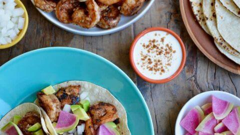 Top down view of spicy shrimp tacos, spicy shrimp, tortillas, sour cream, avocado and cilantro