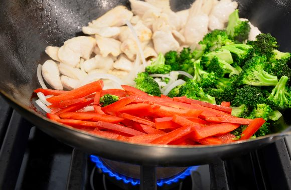 Wok containing sliced red bell pepper, broccoli florets and chicken over oven burner