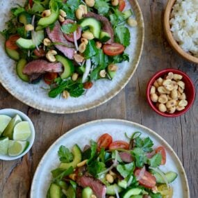 Two plates containing easy Thai Beef Salad with Lime Dressing garnished with peanuts