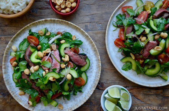 Two plates containing Thai Beef Salad next to two small bowls containing peanuts and limes