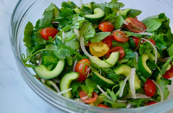 Glass bowl with Thai salad ingredients: cucumber, shallots, mint, cilantro and cherry tomatoes