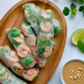 A wood serving plate containing Thai Spring Rolls with peanut sauce, limes and veggies around it