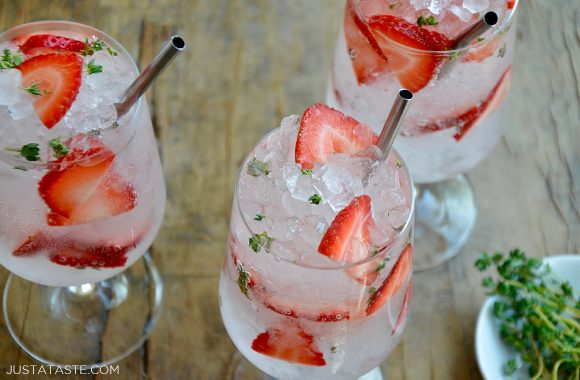 Three glasses filled with sparkling soda and sliced strawberries