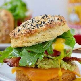 The Ultimate Biscuit Breakfast Sandwich with arugula, avocado, bacon and tomato
