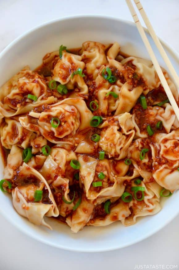 Top down view of white bowl containing spicy chicken wontons with chopsticks