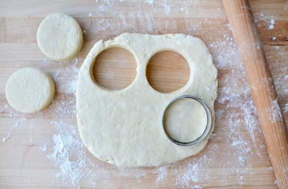Rolling pin next to biscuit dough with circular cookie cutter