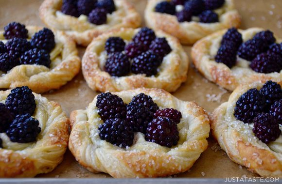 Rows of blackberry cream cheese pastries on a baking sheet
