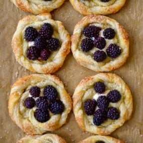 A baking sheet with brown parchment paper and blackberry pastries