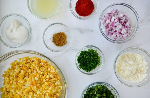 Small glass bowls containing elote corn ingredients