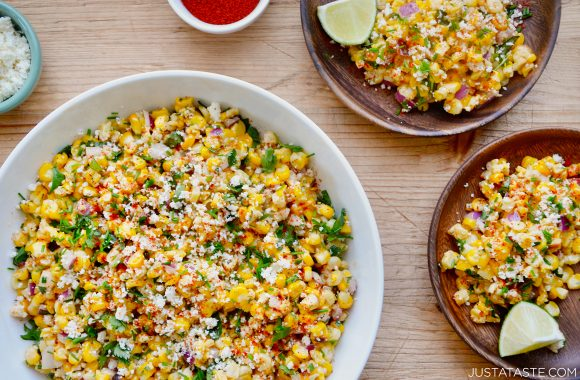 Easy Elote Corn Salad with lime wedges and crumbled Cotija cheese
