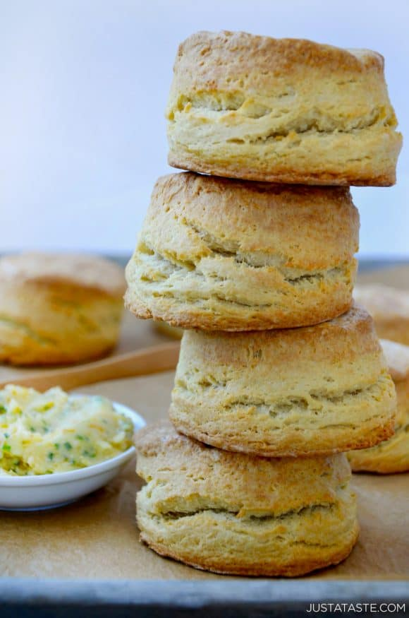 Easy Homemade Buttermilk Biscuits stacked four high next to dish with honey butter