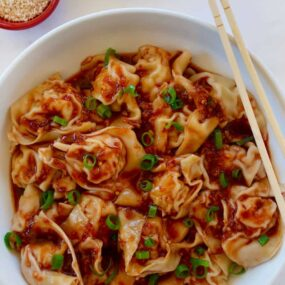 Bowl containing Spicy Chicken Wontons with chopsticks next to small red bowl with sesame seeds