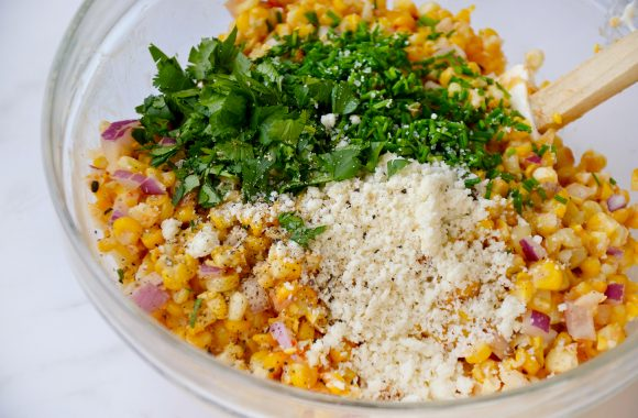 Glass bowl containing corn, red onion, cilantro, Cotija cheese and pepper