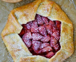 Strawberries and Cream Galette next to forks, bowl with whipped cream and sift containing powdered sugar