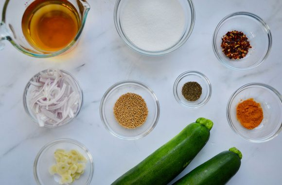 Glass bowls filled with ingredients to make zucchini pickles