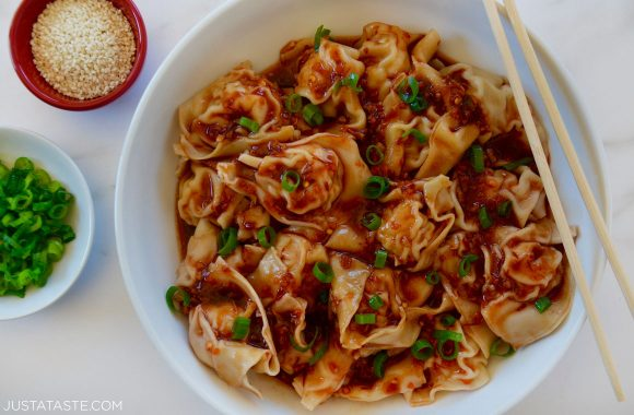 Bowl containing Spicy Chicken Wontons with chopsticks garnished with scallions and sesame seeds