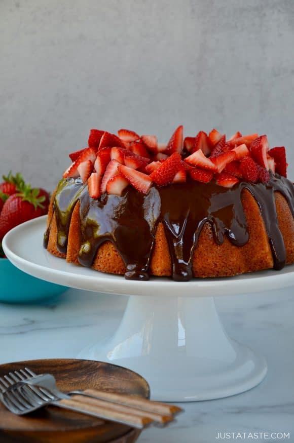 A cake with chocolate frosting and strawberries on a white cake stand