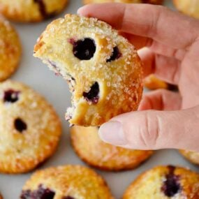 A hand holding a blueberry hand pie with more hand pies in the background