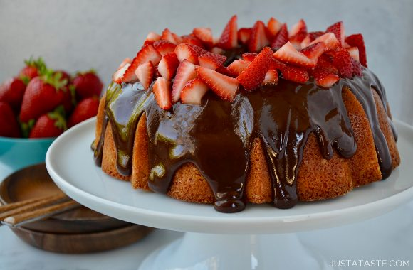 A white cake plate containing a cake topped with chocolate glaze and strawberries