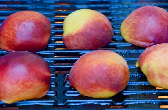 Peach halves being grilled