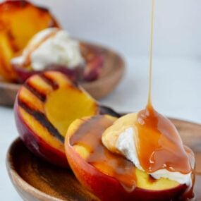 Grilled peach sundaes dripping with boozy caramel sauce and topped with vanilla ice cream