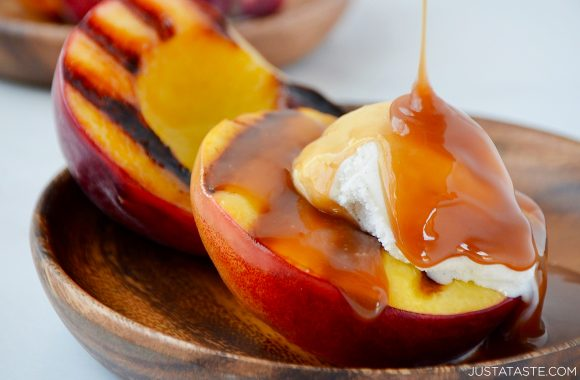 Close-up view of easy grilled peaches topped with ice cream and boozy caramel sauce
