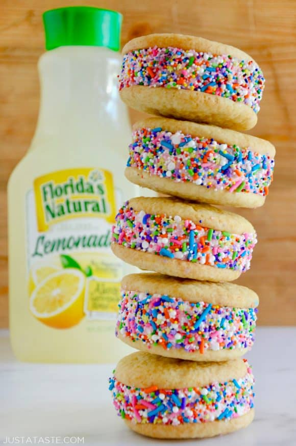 A stack of lemon ice cream sandwiches coated in sprinkles with a bottle of lemonade behind them