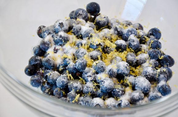 A glass bowl containing blueberries, lemon zest and sugar