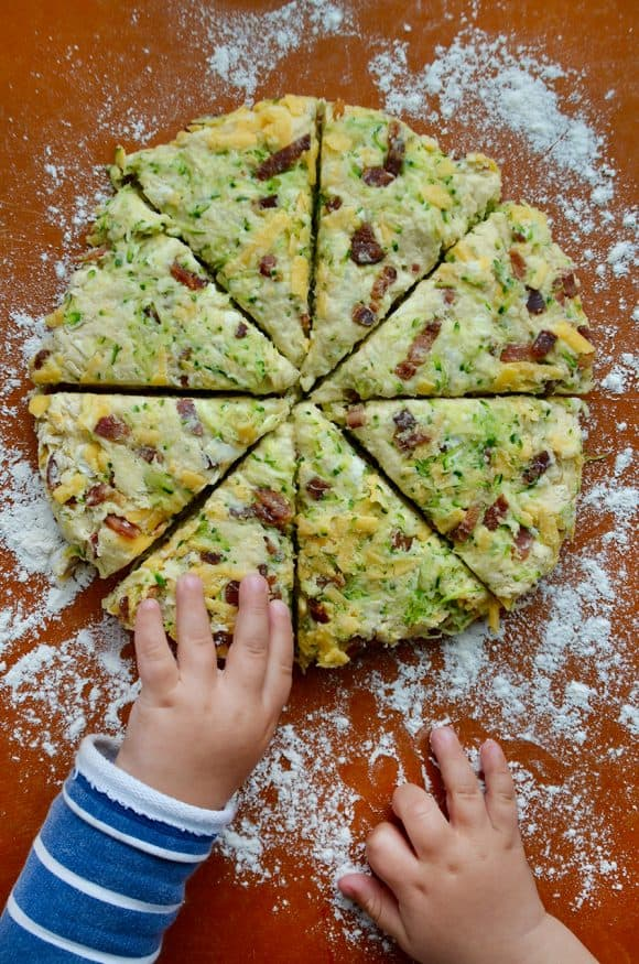 Child's hands reaching for zucchini bacon cheddar scones on generously floured cutting board
