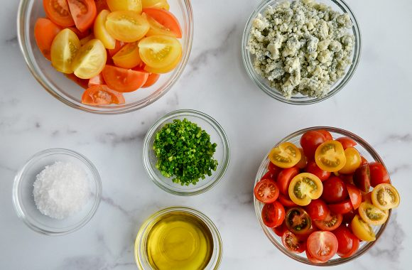Small glass bowls filled with cherry tomatoes, chives, blue cheese, olive oil and salt