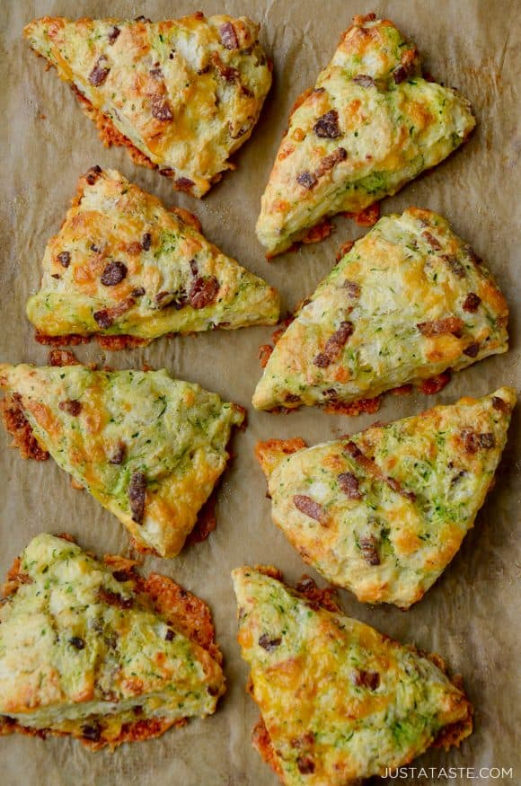 Top down view of eight savory Zucchini Bacon Cheddar Scones on brown parchment paper