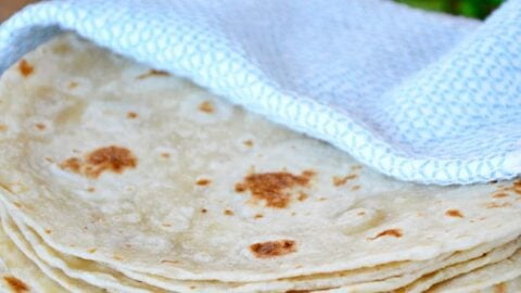 A stack of homemade tortillas in a blue towel with cheese and cilantro in the background