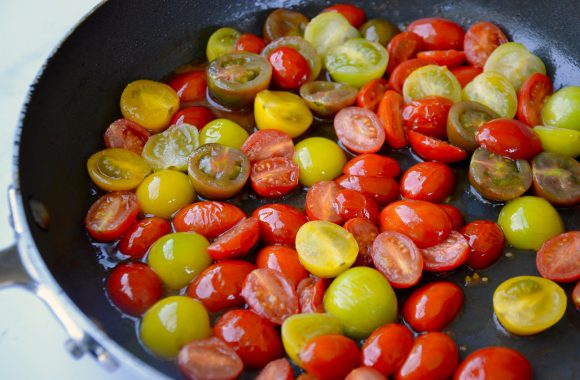 Skillet containing blistered halved cherry tomatoes
