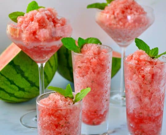 Various sized cocktail glasses filled with Boozy Watermelon Granita and fresh mint