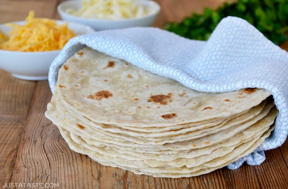 A stack of homemade flour tortillas in a blue towel