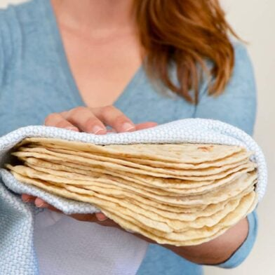 Kelly Senyei holding a stack of homemade tortillas in a blue napkin