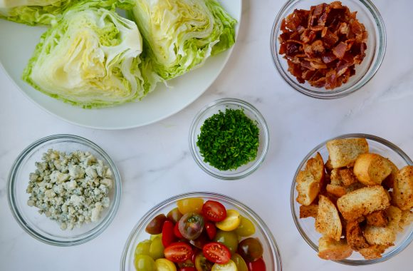 Homemade iceberg wedge salad ingredients in various sized glass bowls