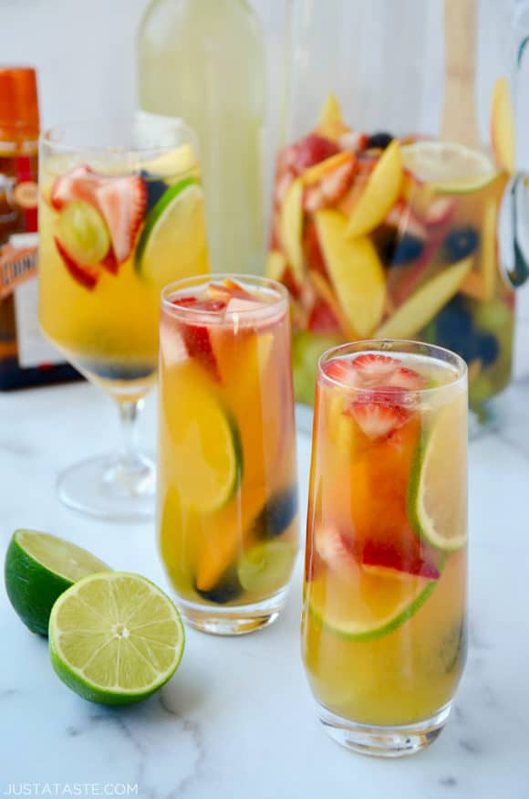 Various glasses filled with the best homemade white sangria with strawberries, limes, apples, grapes, blackberries and peaches