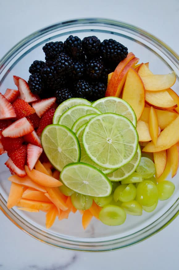 Glass bowl with sliced limes, blackberries, apples, grapes, peaches and strawberries