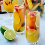 Various cocktail glasses filled with fresh fruit and white sangria in front of a pitcher filled with white sangria and a bottle of white wine.