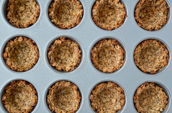 Top down view of freshly baked muffin tin filled with granola