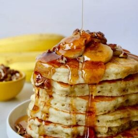 A tall stack of banana pancakes topped with bananas and maple syrup